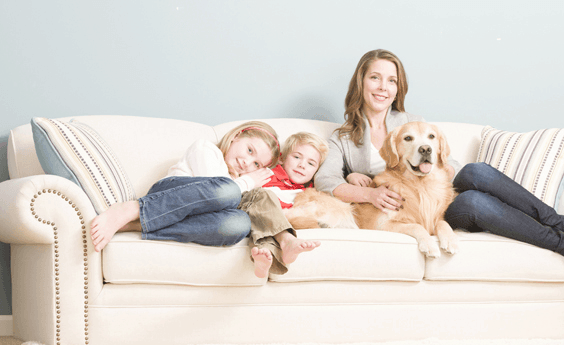 Image of Mother & Daughters sat on a clean Sofa Upholstery with pet dog in Sheffield.